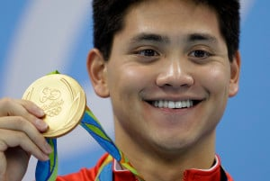 Singapore's Joseph Schooling shows off his gold medal in the men's 100-meter butterfly medals ceremony during the swimming competitions at the 2016 Summer Olympics, Friday, Aug. 12, 2016, in Rio de Janeiro, Brazil. (AP Photo/Michael Sohn)
